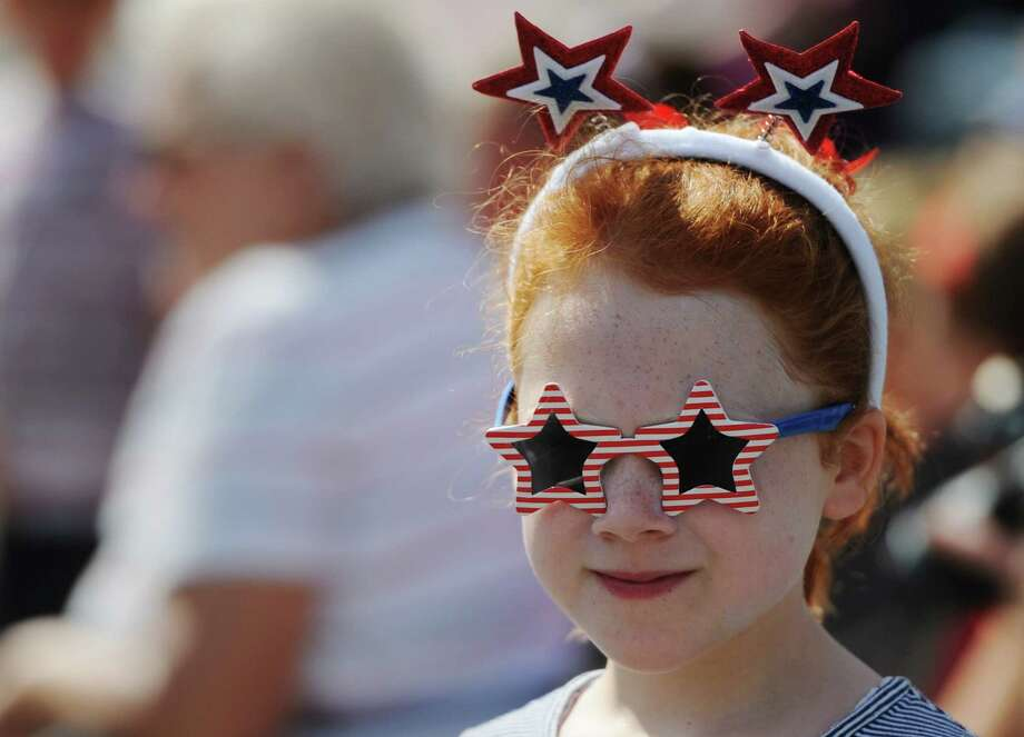 Julia Molloy, 8, of New Fairfield, wears patriotic glasses to watch the Annual Independence Day Parade in New Fairfield, Conn. on Thursday, July 4, 2013.  Hundreds of people lined the streets of downtown New Fairfield to watch the festivities, sponsored by the New Fairfield Lions Club. Photo: Tyler Sizemore / The News-Times