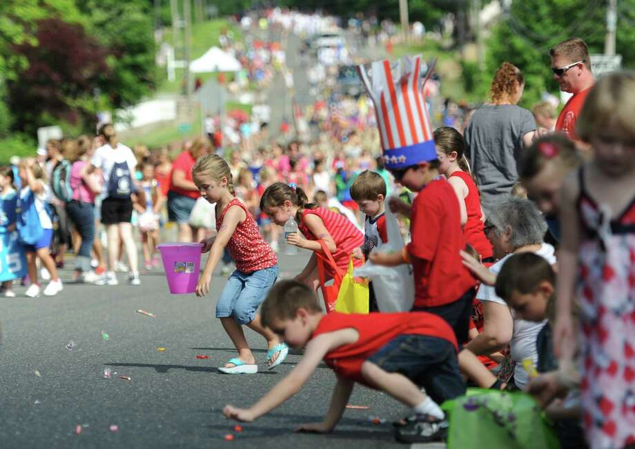 Children scramble to pick up candy at the Annual Independence Day Parade in New Fairfield, Conn. on Thursday, July 4, 2013.  Hundreds of people lined the streets of downtown New Fairfield to watch the festivities, sponsored by the New Fairfield Lions Club. Photo: Tyler Sizemore / The News-Times