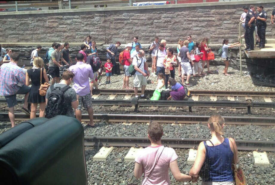 Passengers evacuated from a Metro-North commuter train after a fire was reported on the rear car Thursday, July 4, 2013. No injuries were reported, but service along the New Haven Line has been suspended indefinitely. Photo: Contributed Photo