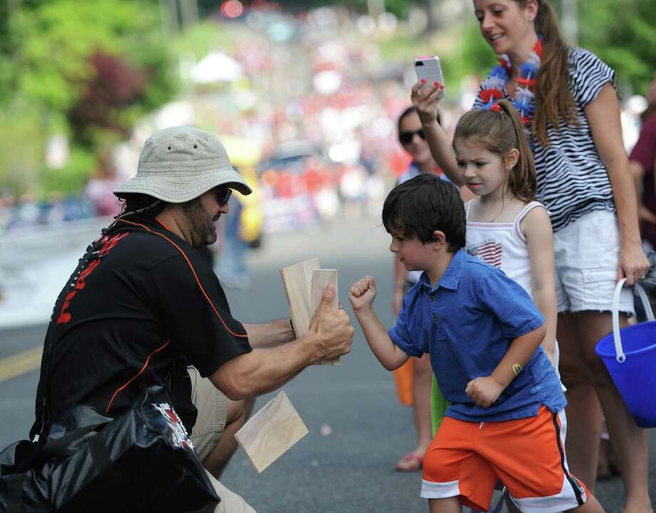 Benjamin Schwarz, 4, of New Fairfield, punches through a board held by Rory Langguth, of Tae Kwon Do New Fairfield, at the Annual Independence Day Parade in New Fairfield, Conn. on Thursday, July 4, 2013.  Hundreds of people lined the streets of downtown New Fairfield to watch the festivities, sponsored by the New Fairfield Lions Club. Photo: Tyler Sizemore / The News-Times