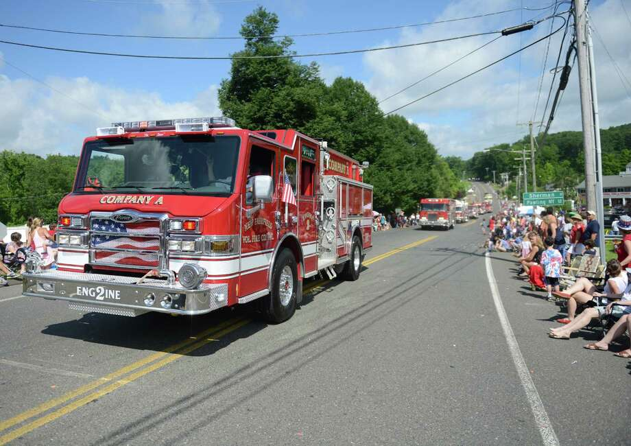 A New Fairfield fire engine drives through the Annual Independence Day Parade in New Fairfield, Conn. on Thursday, July 4, 2013.  Hundreds of people lined the streets of downtown New Fairfield to watch the festivities, sponsored by the New Fairfield Lions Club. Photo: Tyler Sizemore / The News-Times