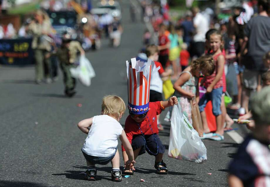 Emmett Naumann, left, 3, of New Fairfield, and Joseph John Deluise, 5, of New Fairfield, pick up candy at the Annual Independence Day Parade in New Fairfield, Conn. on Thursday, July 4, 2013.  Hundreds of people lined the streets of downtown New Fairfield to watch the festivities, sponsored by the New Fairfield Lions Club. Photo: Tyler Sizemore / The News-Times