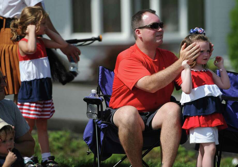 Parade watchers cover their ears as fire engines beep at the crowd during the Annual Independence Day Parade in New Fairfield, Conn. on Thursday, July 4, 2013.  Hundreds of people lined the streets of downtown New Fairfield to watch the festivities, sponsored by the New Fairfield Lions Club. Photo: Tyler Sizemore / The News-Times