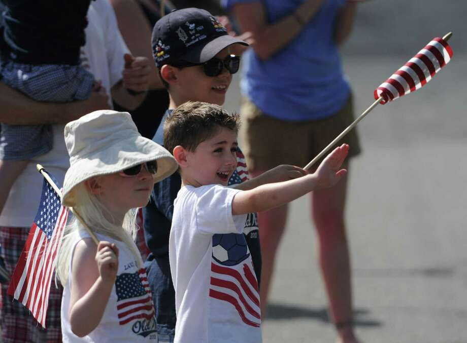 From left, Lucy Hines, 5, Slate Hill, N.Y., nick Gizzo, 4, New Fairfield, and Andrew Hines, 7, Slate Hill, N.Y., cheer for the Annual Independence Day Parade in New Fairfield, Conn. on Thursday, July 4, 2013.  Hundreds of people lined the streets of downtown New Fairfield to watch the festivities, sponsored by the New Fairfield Lions Club. Photo: Tyler Sizemore / The News-Times