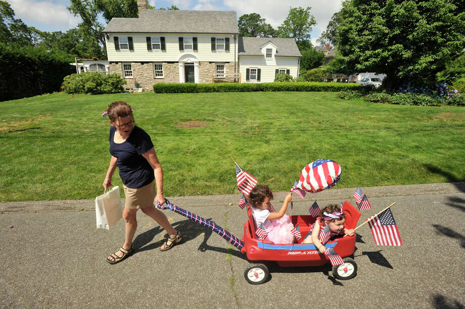 Peg Hickey pulls her granddaughters Koreena Hickey, 4, center, and Claire Hickey, 2, down Stamford Avenue during the Shippan Point Association July 4 Bike Parade in Stamford on Thursday, July 4, 2013. Photo: Jason Rearick / Stamford Advocate