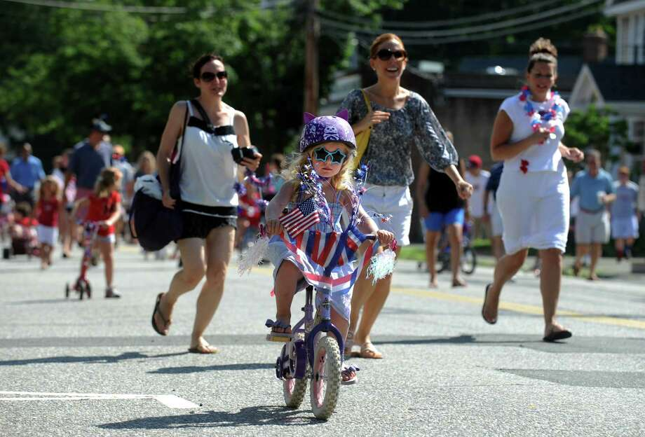 Four-year-old Sophie Jacques, of Westport, pedals down Pequot Avenue during the annual 4th of July Bike Parade and Old Fashioned Lawn Games Thursday, July 04, 2013 in Southport, Conn. Photo: Autumn Driscoll / Connecticut Post