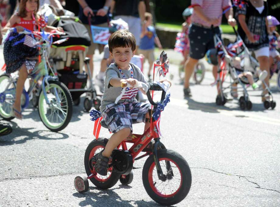 Three-year-old Alex Fuchs, of Fairfield, pedals down Pequot Avenue during the annual 4th of July Bike Parade and Old Fashioned Lawn Games Thursday, July 04, 2013 in Southport, Conn. Photo: Autumn Driscoll / Connecticut Post