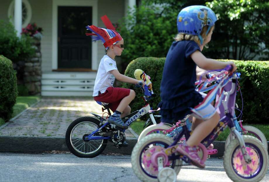 Six-year-old Pierce McDonald, of Fairfield, pedals down Pequot Avenue during the annual 4th of July Bike Parade and Old Fashioned Lawn Games Thursday, July 04, 2013 in Southport, Conn. Photo: Autumn Driscoll / Connecticut Post