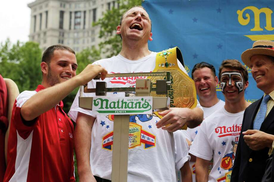 Joey Chestnut laughs as he stands on the scale during the official weigh-in for the Nathan's Fourth of July hot dog eating contest, Wednesday, July 3, 2013 at City Hall park in New York.  (AP Photo/Mary Altaffer) Photo: Mary Altaffer, Associated Press / AP