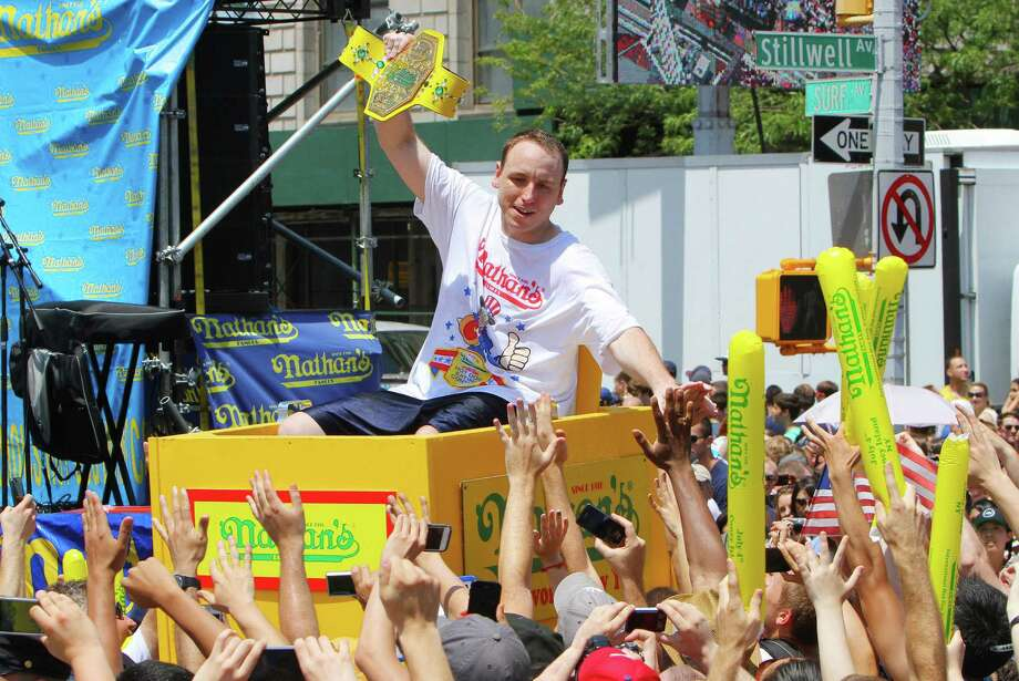 NEW YORK, NY- JULY 04:  Joey Chestnut is carried through the crowds as the champion is introduced before the start of the Nathan's Famous Fourth of July Hot Dog Eating Contest at Nathan's Famous in Coney Island on July 4, 2013 in the Brooklyn borough of New York City. Chestnut, of San Jose, California, ate 69 hotdogs in ten minutes to win his seventh straight title. Photo: Monika Graff, Getty Images / 2013 Getty Images