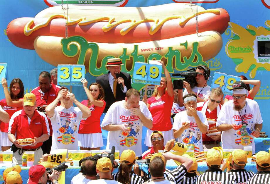 NEW YORK, NY- JULY 04:  (L to R) Tim Janus, Joey Chestnut, Matt Stonie and Bob Shoudt compete in the Nathan's Famous Fourth of July Hot Dog Eating Contest at Nathan's Famous in Coney Island on July 4, 2013 in the Brooklyn borough of New York City. Chestnut, of San Jose, California, ate 69 hotdogs in ten minutes to win his seventh straight title. Photo: Monika Graff, Getty Images / 2013 Getty Images