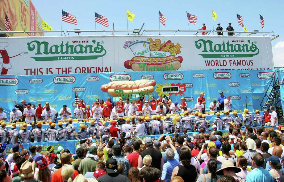 NEW YORK, NY- JULY 04:  People watch the Nathan's Famous Fourth of July Hot Dog Eating Contest at Nathan's Famous in Coney Island on July 4, 2013 in the Brooklyn borough of New York City. Chestnut, of San Jose, California, ate 69 hotdogs in ten minutes to win his seventh straight title. Photo: Monika Graff, Getty Images / 2013 Getty Images