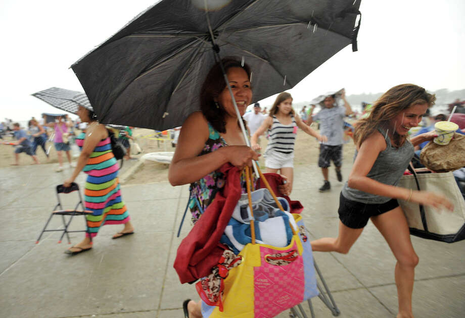 Doris Victorino, center, of Stamford, and others flee the beach to avoid the downpour during the fireworks celebration at Cummings Park beach on Wednesday, July 3, 2013. Photo: Jason Rearick / Stamford Advocate