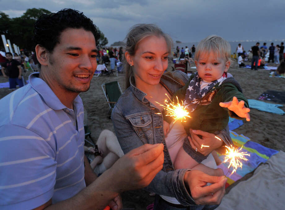 Nelson and Simone Franco light their sparklers for their son, Aaron, during the fireworks celebration at Cummings Park beach on Wednesday, July 3, 2013. Photo: Jason Rearick / Stamford Advocate