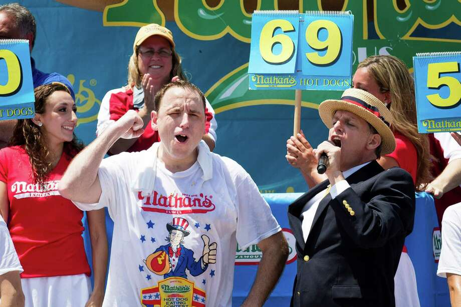 Joey Chestnut, foreground left, wins the Nathan's Famous Fourth of July International Hot Dog Eating contest with a total of 69 hot dogs and buns at Coney Island, Thursday, July 4, 2013, in the Brooklyn borough of New York. (AP Photo/John Minchillo) Photo: John Minchillo, Associated Press / FR170537 AP