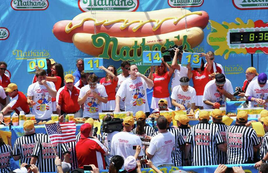 NEW YORK, NY- JULY 04:  Competitors eat hotdogs during the Nathan's Famous Fourth of July Hot Dog Eating Contest at Nathan's Famous in Coney Island on July 4, 2013 in the Brooklyn borough of New York City. Joey Chestnut, of San Jose, California, ate 69 hotdogs in ten minutes to win his seventh straight title. Photo: Monika Graff, Getty Images / 2013 Getty Images