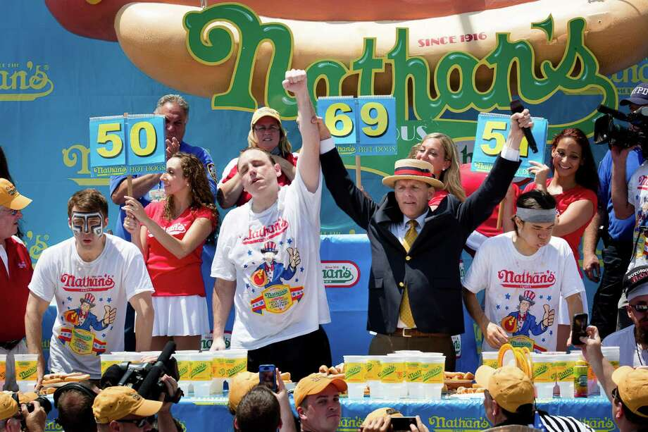 Joey Chestnut, center, wins the Nathan's Famous Fourth of July International Hot Dog Eating contest with a total of 69 hot dogs and buns, alongside Tim Janus, left, and Matt Stonie, right, at Coney Island, Thursday, July 4, 2013, in the Brooklyn borough of New York. (AP Photo/John Minchillo) Photo: John Minchillo, Associated Press / FR170537 AP