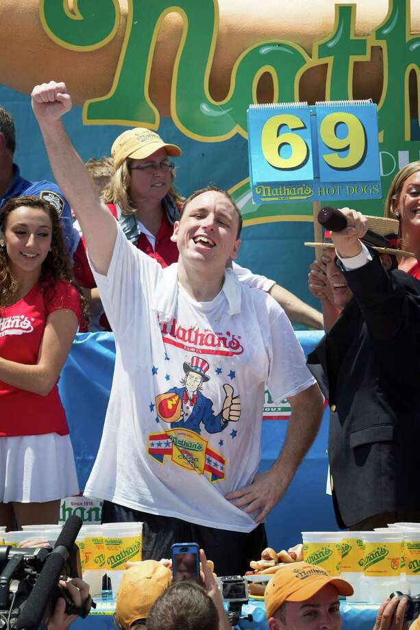 Joey Chestnut, center, wins the Nathan's Famous Fourth of July International Hot Dog Eating contest with a total of 69 hot dogs and buns at Coney Island, Thursday, July 4, 2013, in the Brooklyn borough of New York. (AP Photo/John Minchillo) Photo: John Minchillo, Associated Press / FR170537 AP