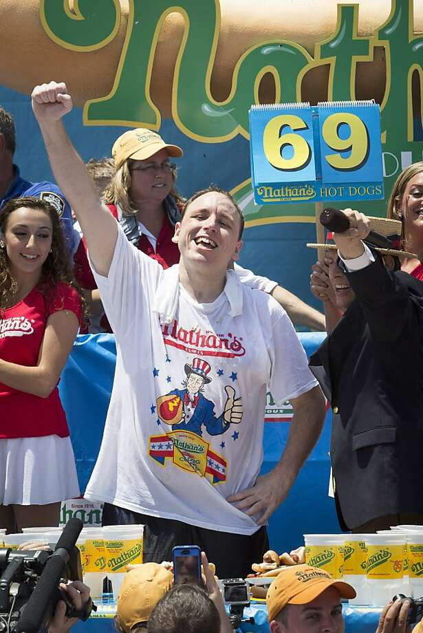 Joey Chestnut, center, wins the Nathan's Famous Fourth of July International Hot Dog Eating contest with a total of 69 hot dogs and buns at Coney Island, Thursday, July 4, 2013, in the Brooklyn borough of New York. (AP Photo/John Minchillo) Photo: John Minchillo, Associated Press