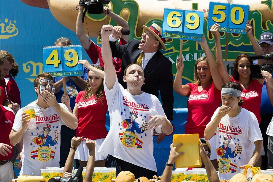Joey Chestnut, center, wins the Nathan's Famous Fourth of July International Hot Dog Eating contest with a total of 69 hot dogs and buns, alongside Tim Janus, left, and Matt Stonie, right, Thursday, July 4, 2013 at Coney Island, in the Brooklyn borough of New York. (AP Photo/John Minchillo) Photo: John Minchillo, Associated Press