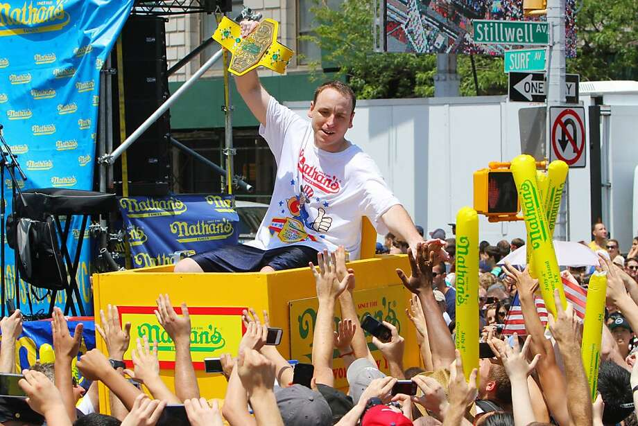 NEW YORK, NY- JULY 04:  Joey Chestnut is carried through the crowds as the champion is introduced before the start of the Nathan's Famous Fourth of July Hot Dog Eating Contest at Nathan's Famous in Coney Island on July 4, 2013 in the Brooklyn borough of New York City. Chestnut, of San Jose, California, ate 69 hotdogs in ten minutes to win his seventh straight title. (Photo by Monika Graff/Getty Images) Photo: Monika Graff, Getty Images