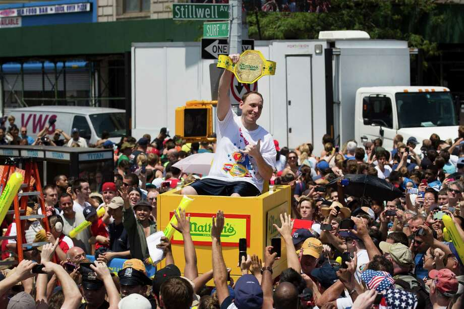 Joey Chestnut, six time winner of the Nathan's Famous Fourth of July International Hot Dog Eating contest, is carried to the competition stage through a crowd of fans, Thursday, July 4, 2013 at Coney Island, in the Brooklyn borough of New York. (AP Photo/John Minchillo) Photo: John Minchillo, Associated Press / FR170537 AP