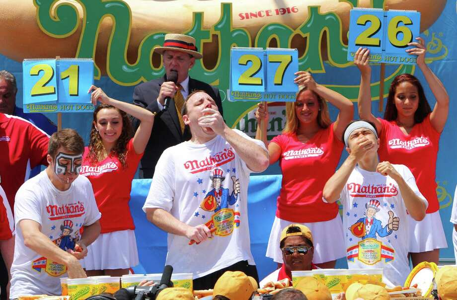 NEW YORK, NY- JULY 04:  (L to R) Tim Janus, Joey Chestnut, and Matt Stonie compete in the Nathan's Famous Fourth of July Hot Dog Eating Contest at Nathan's Famous in Coney Island on July 4, 2013 in the Brooklyn borough of New York City. Chestnut, of San Jose, California, ate 69 hotdogs in ten minutes to win his seventh straight title. Photo: Monika Graff, Getty Images / 2013 Getty Images