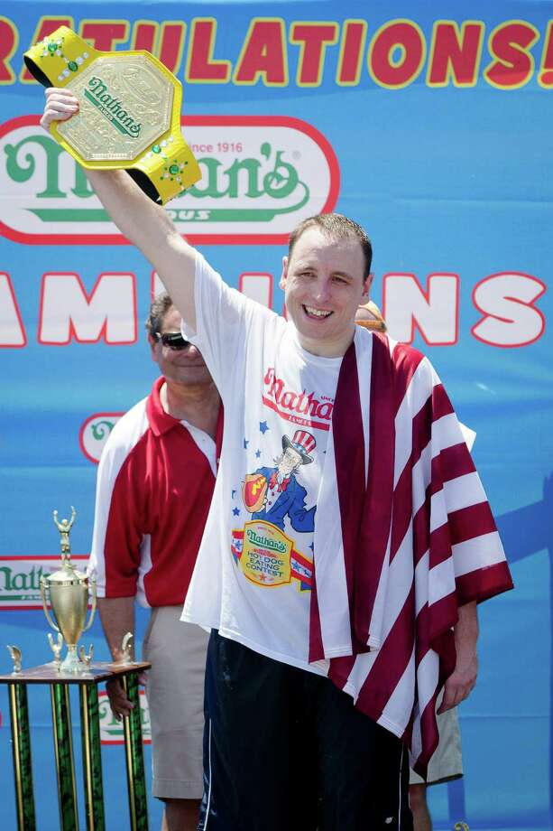 Joey Chestnut holds the Mustard Yellow belt as he celebrates winning the Nathan's Famous Fourth of July International Hot Dog Eating contest with a total of 69 hot dogs and buns, Thursday, July 4, 2013 at Coney Island, in the Brooklyn borough of New York. (AP Photo/John Minchillo) Photo: John Minchillo, Associated Press / FR170537 AP