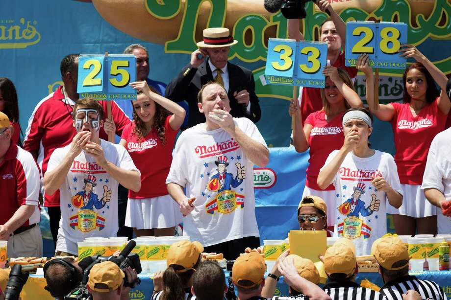 From left, Tim Janus, Joey Chestnut, and Matt Stonie compete in the Nathan's Famous Fourth of July International Hot Dog Eating contest at Coney Island, Thursday, July 4, 2013 at Coney Island, in the Brooklyn borough of New York. (AP Photo/John Minchillo) Photo: John Minchillo, Associated Press / FR170537 AP