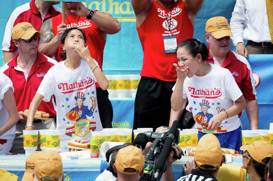 Juliet Lee, left, and Sonya Thomas compete in the Nathan's Famous Fourth of July International Hot Dog Eating contest at Coney Island, Thursday, July 4, 2013, in the Brooklyn borough of New York. Thomas won the competition with 36 and three quarters hot dogs and buns. (AP Photo/John Minchillo) Photo: John Minchillo, Associated Press / FR170537 AP