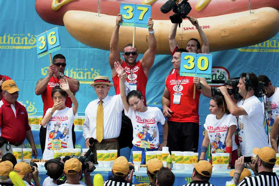Sonya Thomas, center, wins the Nathan's Famous Fourth of July International Hot Dog Eating contest alongside Juliet Lee, left, and Michelle Lesco, right, at Coney Island, Thursday, July 4, 2013, in the Brooklyn borough of New York. (AP Photo/John Minchillo) Photo: John Minchillo, Associated Press / FR170537 AP