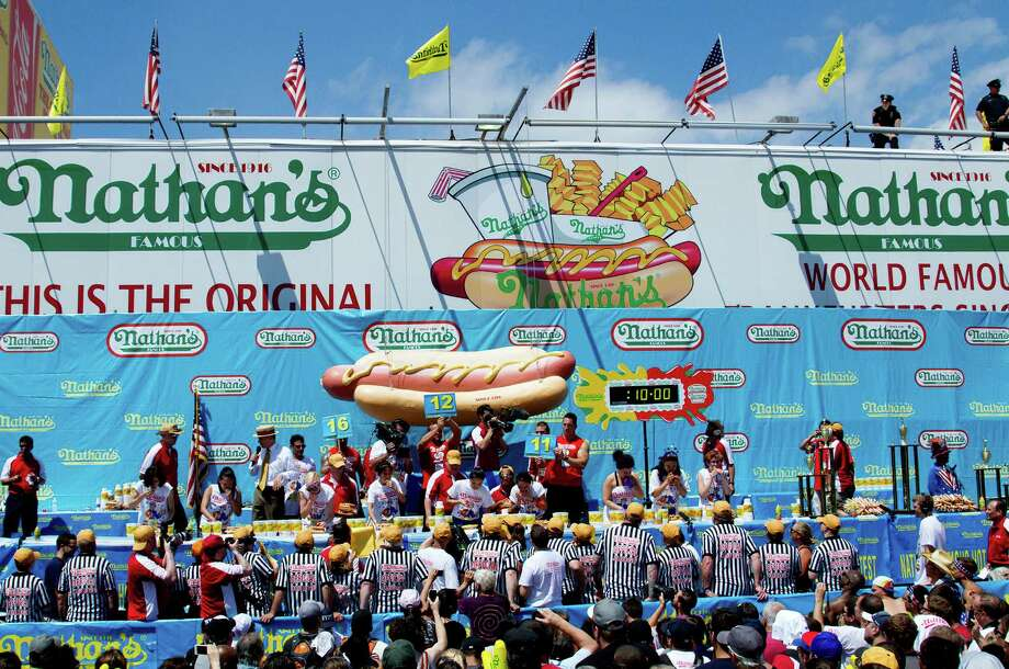 NEW YORK, NY- JULY 04:  People gather on the corner of Surf and Stillwell Avenues to watch the women's division of the Nathan's Famous Fourth of July Hot Dog Eating Contest at Nathan's Famous in Coney Island on July 4, 2013 in the borough of Brooklyn in New York City. Participants in the annual have just ten minutes to down as many hotdogs and buns as they can. Photo: Monika Graff, Getty Images / 2013 Getty Images