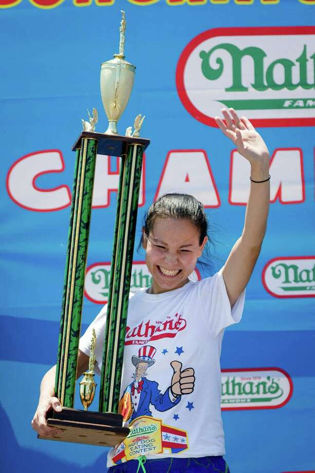 Sonya Thomas holds the first place trophy after winning the Nathan's Famous Fourth of July International Hot Dog Eating contest with a total of 36 and three quarters hot dogs and buns at Coney Island, Thursday, July 4, 2013, in the Brooklyn borough of New York. (AP Photo/John Minchillo) Photo: John Minchillo, Associated Press / FR170537 AP