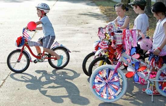 Hudson Leslie, 6, rides his bike as he and children wait for judging in the bike decoration contest before the Kingwood Civic Club 4th of July Parade Thursday, July 4, 2013, in Kingwood. Photo: Melissa Phillip, Houston Chronicle / © 2013  Houston Chronicle