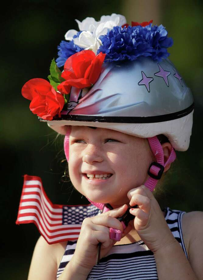Cate Leslie, 7, puts on her helmet as she waits for judging in the bike decoration contest before the Kingwood Civic Club 4th of July Parade Thursday, July 4, 2013, in Kingwood. Photo: Melissa Phillip, Houston Chronicle / © 2013  Houston Chronicle