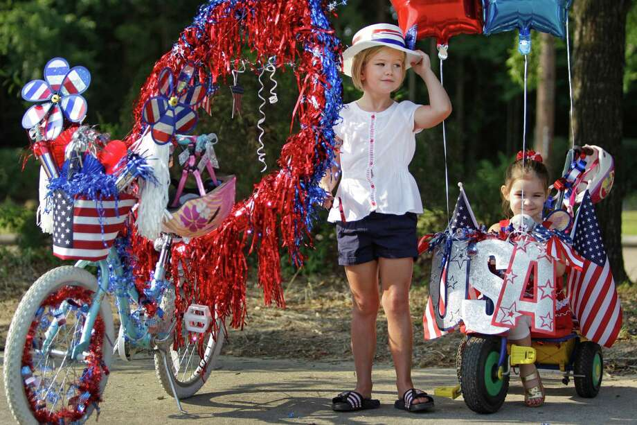 Meredith Schuch, 7, and her sister, Caroline Schuch, 3, wait for judging in the bike decoration contest before the Kingwood Civic Club 4th of July Parade Thursday, July 4, 2013, in Kingwood.  Meredith placed first in the girls'  division. Photo: Melissa Phillip, Houston Chronicle / © 2013  Houston Chronicle