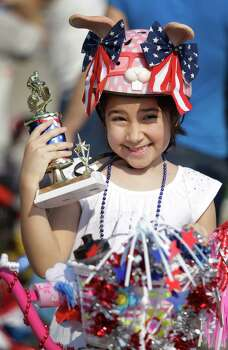 Chloe Alvarez, 7, poses for her parents to take a photo with her third place trophy she won in the bike decoration contest before the Kingwood Civic Club 4th of July Parade Thursday, July 4, 2013, in Kingwood. Photo: Melissa Phillip, Houston Chronicle / © 2013  Houston Chronicle