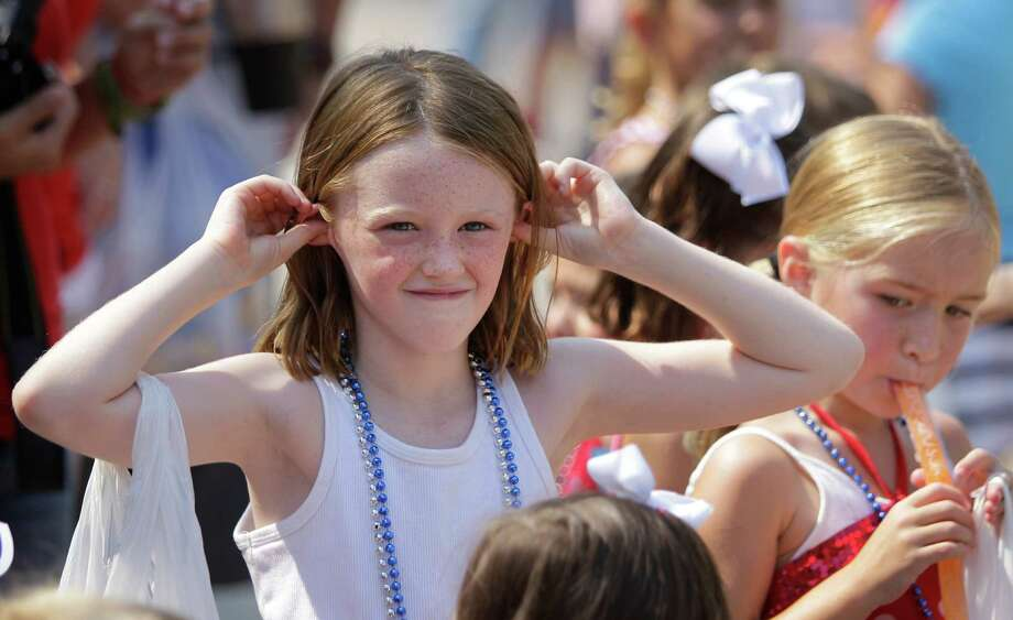 Abby McAdams, 8, covers her ears during the blare of a fire truck siren during the Kingwood Civic Club 4th of July Parade Thursday, July 4, 2013, in Kingwood. Photo: Melissa Phillip, Houston Chronicle / © 2013  Houston Chronicle