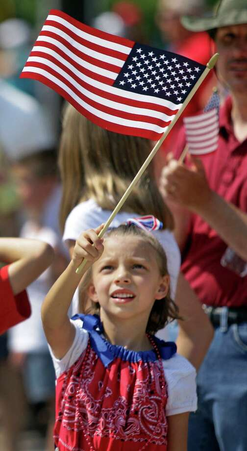 Autumn Turner, 6, waves a flag during the Kingwood Civic Club 4th of July Parade Thursday, July 4, 2013, in Kingwood. Photo: Melissa Phillip, Houston Chronicle / © 2013  Houston Chronicle