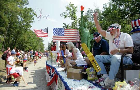 Ray Anderson, right, and other members of the Kingwood Service Association throw beads and candy from their float during the Kingwood Civic Club 4th of July Parade Thursday, July 4, 2013, in Kingwood. Photo: Melissa Phillip, Houston Chronicle / © 2013  Houston Chronicle