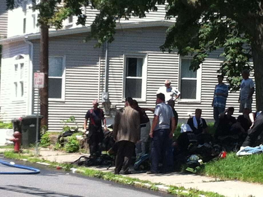 Cohoes firefighters cool off in shade after extinguishing fire at 20 Schuyler St. (Kenneth C. Crowe/Times Union)