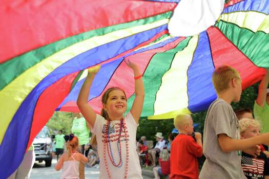 Sarah West, 8, left, and other children play under a colorful parachute during the Kingwood Civic Club 4th of July Parade Thursday, July 4, 2013, in Kingwood. Photo: Melissa Phillip, Houston Chronicle / © 2013  Houston Chronicle