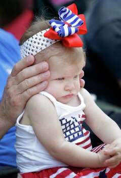 Craig Clowe covers the ears of his 8-month-old granddaughter, Emma Clowe, as sirens blare from passing fire trucks during the Kingwood Civic Club 4th of July Parade Thursday, July 4, 2013, in Kingwood. Photo: Melissa Phillip, Houston Chronicle / © 2013  Houston Chronicle