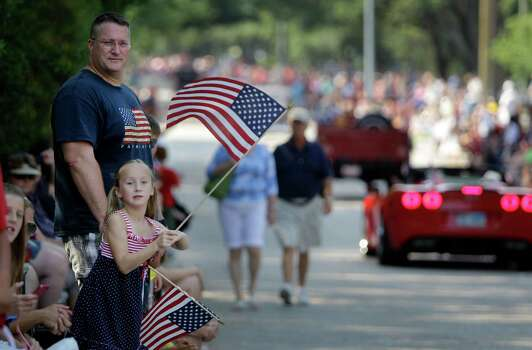 Julia Dalton, 7, and her dad, Scott Dalton wave flags during the Kingwood Civic Club 4th of July Parade Thursday, July 4, 2013, in Kingwood. Photo: Melissa Phillip, Houston Chronicle / © 2013  Houston Chronicle