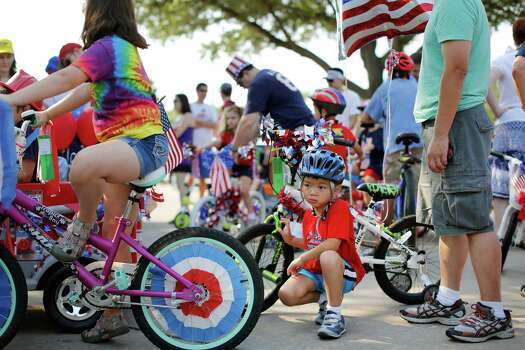 5-year-old Nicholas Lam waits patiently next to his bike and father, David, right, before the start of an Independence Day parade, Thursday, July 4, 2013 in Bellaire, Texas. (PHOTO BY TODD SPOTH) Photo: © TODD SPOTH PHOTOGRAPHY, LLC / © TODD SPOTH PHOTOGRAPHY, LLC