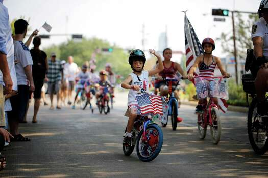 Bike parade participants wave to the gathered crowd, during an Independence Day parade, Thursday, July 4, 2013 in Bellaire, Texas. (PHOTO BY TODD SPOTH) Photo: © TODD SPOTH PHOTOGRAPHY, LLC / © TODD SPOTH PHOTOGRAPHY, LLC
