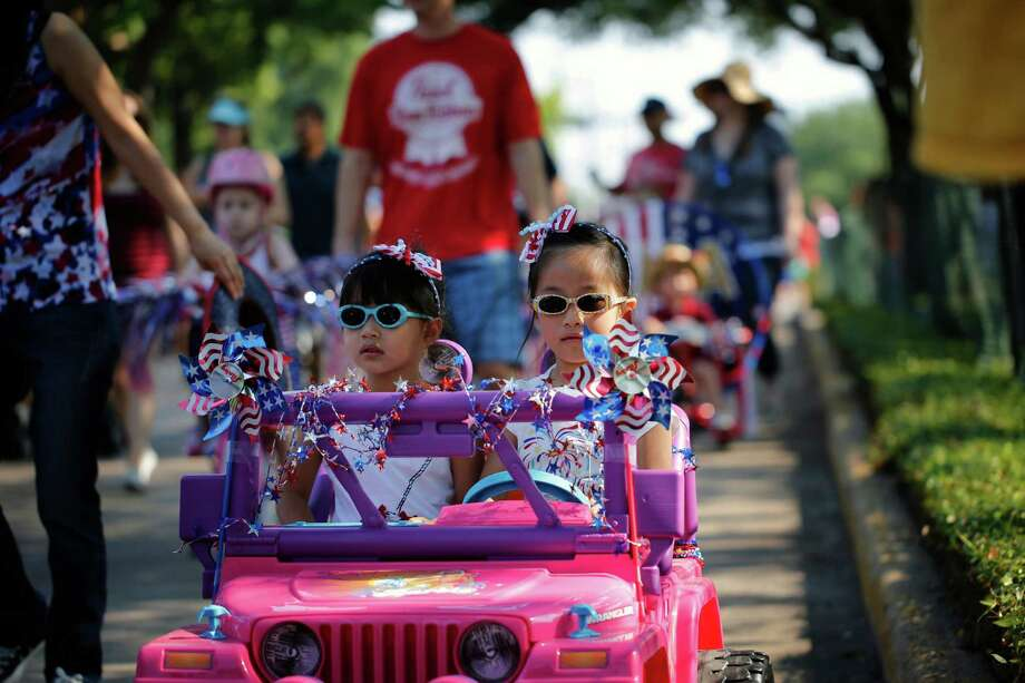 Sisters, Julie and Sophie Tang ride in their motorized toy car, during an Independence Day parade, Thursday, July 4, 2013 in Bellaire, Texas. (PHOTO BY TODD SPOTH) Photo: © TODD SPOTH PHOTOGRAPHY, LLC / © TODD SPOTH PHOTOGRAPHY, LLC