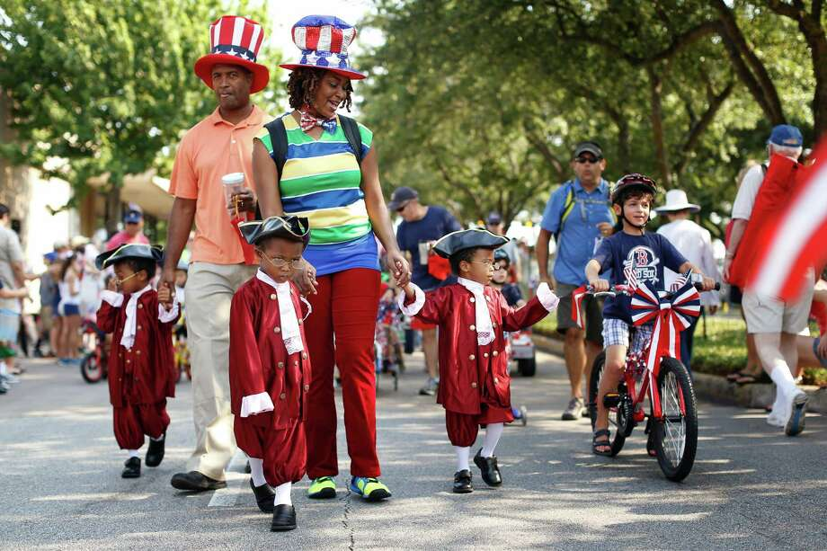Dressed in colonial wear, brothers, from left to right, Quintin, Orrin, and Shemar Adams are led down the parade route by parents, Orrin and Marylin Adams, during an Independence Day parade, Thursday, July 4, 2013 in Bellaire, Texas. (PHOTO BY TODD SPOTH) Photo: © TODD SPOTH PHOTOGRAPHY, LLC / © TODD SPOTH PHOTOGRAPHY, LLC