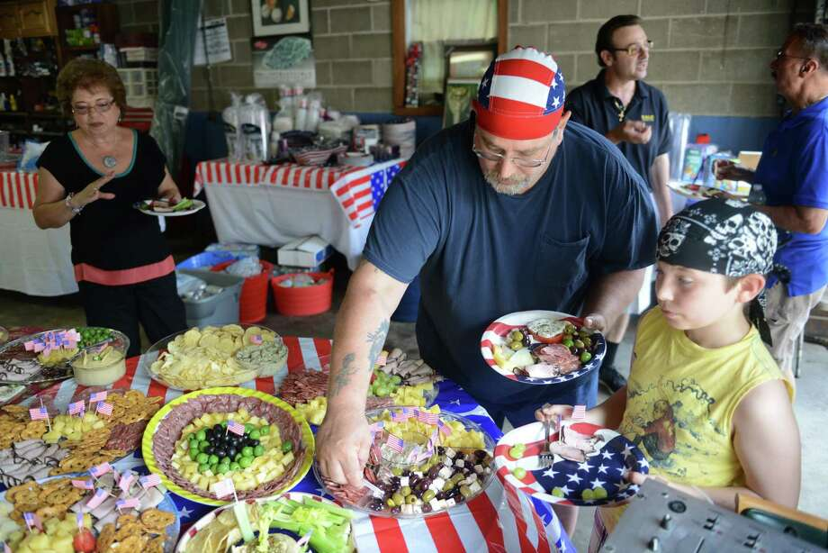 "Mario Dellangelo and Michael Murray, 12, of New Fairfield, grab some food at a Fourth of July party in New Fairfield, Conn. on Thursday, July 4, 2013.  The party, hosted by Gaetano ""Tommy"" Russotti, drew over 100 guests.  Russotti spent over $8,000 this year on food, drinks, decorations and festivities, which included a mariachi band, ice cream truck and a belly dancer.  Russotti has been hosting a Fourth of July party in New Fairfield for over 30 years and it keeps growing every year. Photo: Tyler Sizemore / The News-Times"