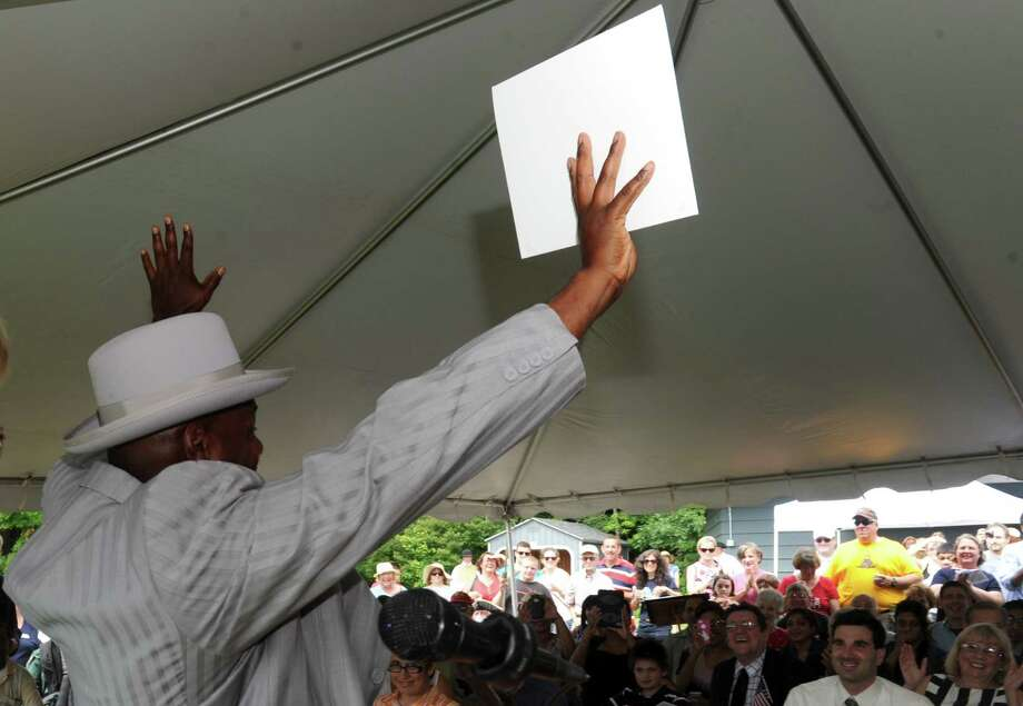 New citizen Steve Anthony Moore raises his arms in celebration after receiving his certificate during a citizenship ceremony  at the Saratoga National Historic Park on Thursday July 4, 2013 in Stillwater, N.Y. (Michael P. Farrell/Times Union) Photo: Michael P. Farrell / 00023028A
